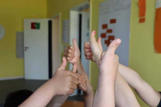 Sechs Kinderhände strecken den Daumen nach oben